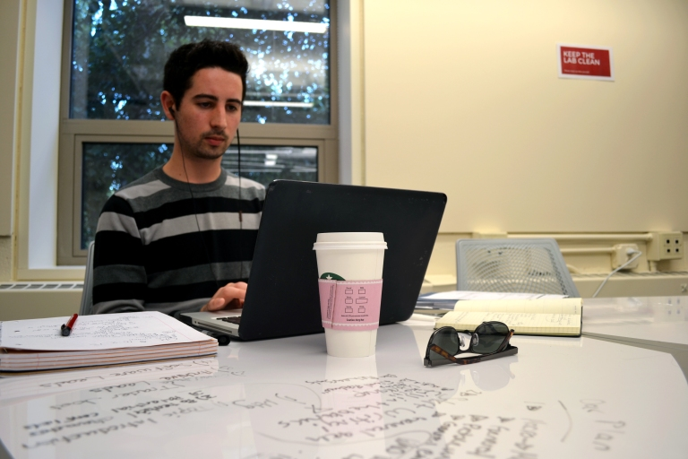 Student leader, Matt from Acting Out, utilizes the workspace in 240.